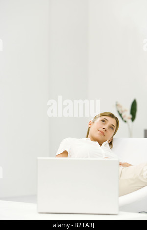 Woman reclining in chair beside laptop computer, looking up, smiling - Stock Photo