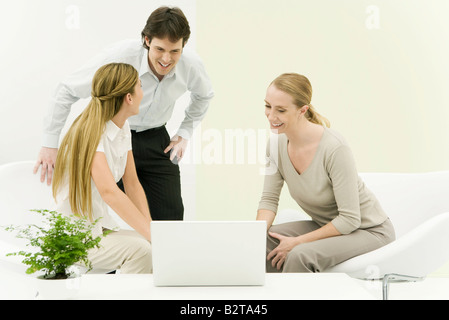 Colleagues in casual office, looking at laptop computer, smiling - Stock Photo