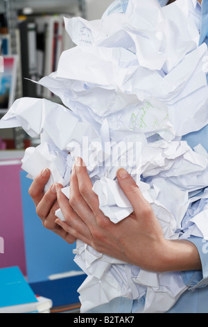 Businesswoman holding crumpled paper - Stock Photo