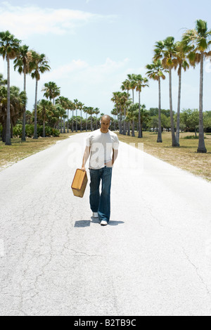 Man walking down center of road, carrying suitcase, listening to headphones - Stock Photo