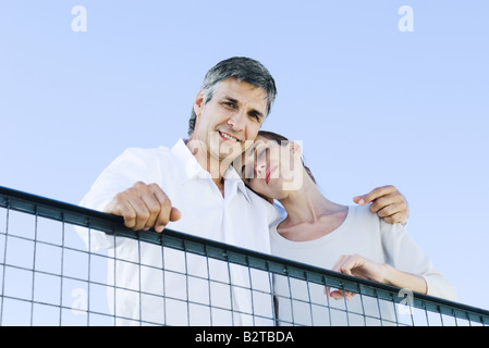 Couple looking down over wire fence at camera, low angle view - Stock Photo