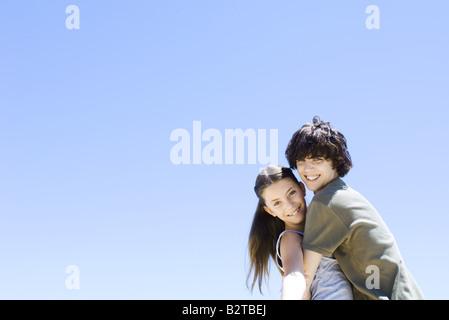 Brother hugging his sister, smiling at camera - Stock Photo