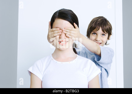 Brother covering his sisters eyes with his hands, smiling - Stock Photo
