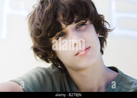 Teenage boy looking away, head tilted, portrait - Stock Photo