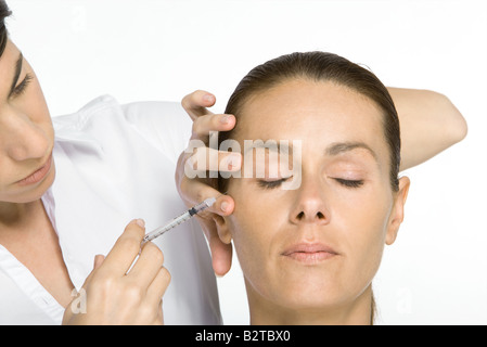 Woman receiving Botox injection, eyes closed - Stock Photo