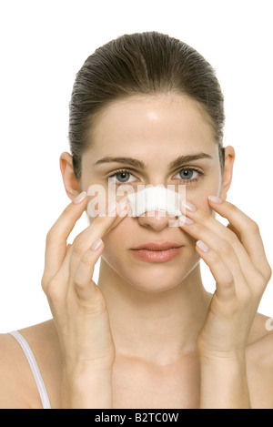 Young woman with bandaged nose, touching face, portrait - Stock Photo