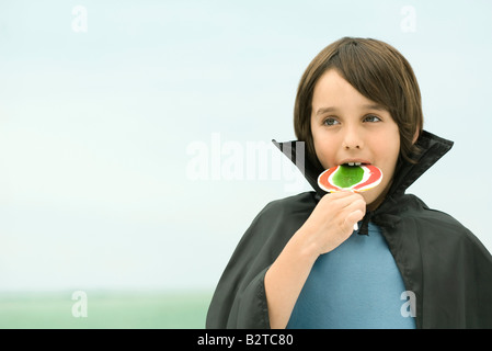 Boy wearing vampire cape, eating large lollipop, portrait - Stock Photo