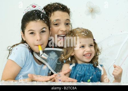 Woman celebrating with daughters on her lap, confetti everywhere - Stock Photo