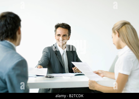 Businessman discussing contract with couple, smiling - Stock Photo