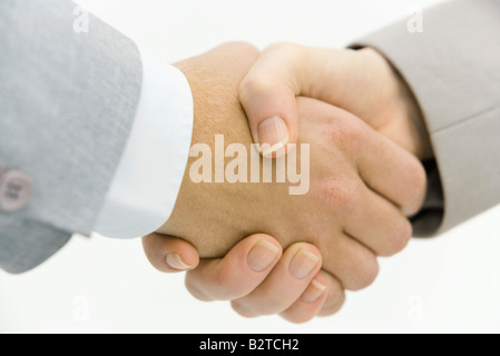 Business partners shaking hands, cropped view, close-up - Stock Photo