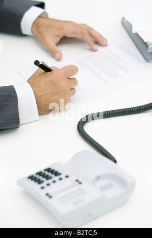 Man signing document, cropped view, landline phone off the hook in foreground - Stock Photo