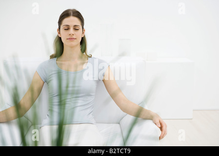 Woman sitting in armchair, eyes closed, plant in foreground - Stock Photo