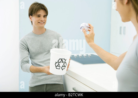Woman aiming paper ball at recycling bin in young man's hands, cropped view - Stock Photo
