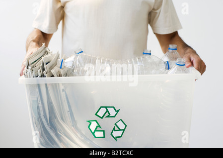 Man carrying recycling bin filled with plastic bottles and newspaper, cropped - Stock Photo