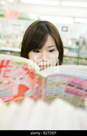 Young Japanese woman reading comic book, selective focus - Stock Photo