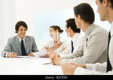 Group of business associates sitting together at conference table, woman smiling at man - Stock Photo