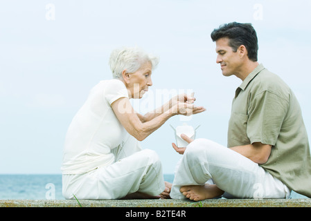 Senior woman and adult son sitting face to face, sharing take out food, side view - Stock Photo