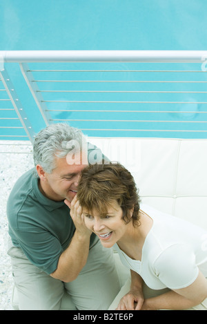 Couple sitting on balcony, man whispering in woman's ear, high angle view - Stock Photo