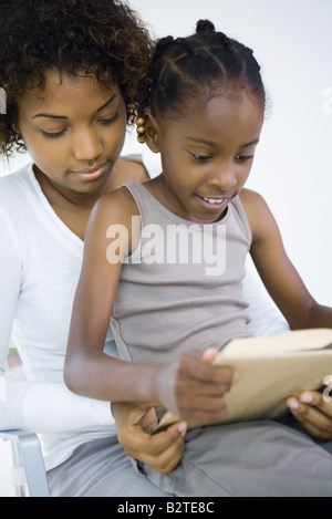 Mother and daughter reading book together, girl sitting on woman's lap, close-up - Stock Photo