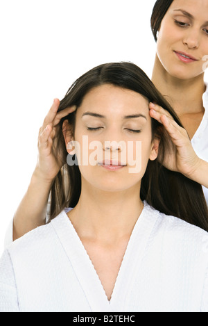 Woman receiving head massage, eyes closed - Stock Photo