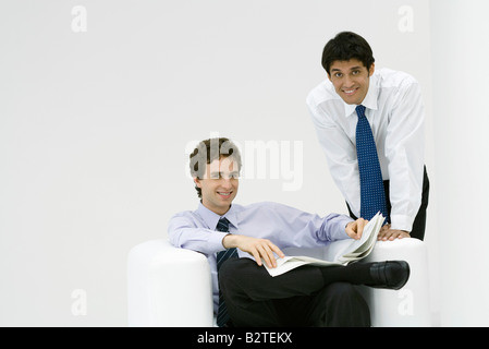 Professional man sitting, holding newspaper, colleague leaning over his shoulder, both smiling at camera - Stock Photo