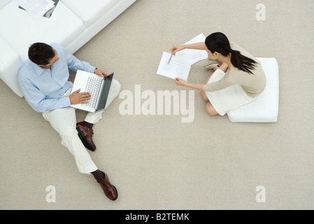 Two colleagues sitting on the ground, discussing document, overhead view - Stock Photo