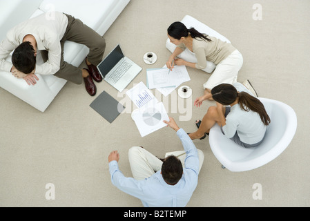 Colleagues discussing documents, two sitting on the floor, one resting head on arms, overhead view - Stock Photo
