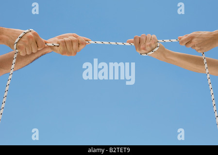Hands playing tug-of-war with rope - Stock Photo