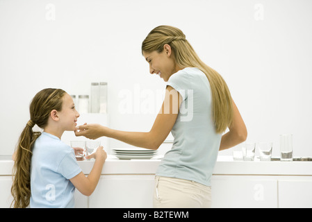 Mother and daughter in kitchen, woman holding girl's chin, both smiling - Stock Photo