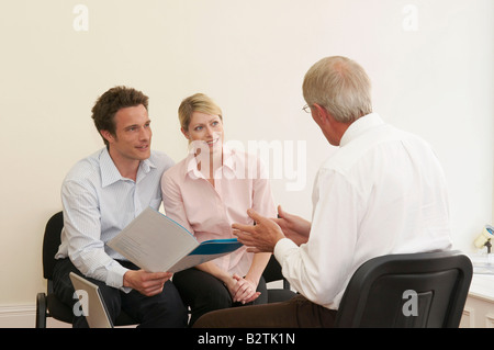 Couple in talks with financial advisor - Stock Photo