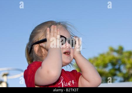 Female Toddler Model Wearing Large, Dark Sunglasses - Stock Photo