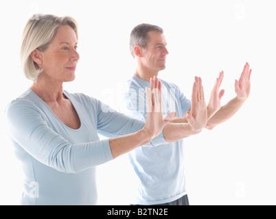 Mature couple doing yoga - Stock Photo