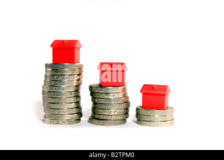 Small red model houses stacked on top of piles of coins isolated objects Property ladder Housing market credit crunch concepts