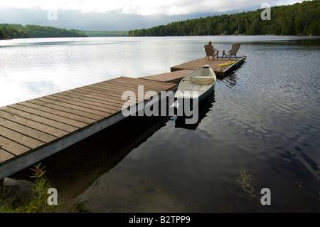 Dock in the early morning on lake in Haliburton Ontario - Stock Photo