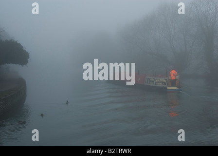 Narrowboat in Thick Fog Sailing on Thames River Oxford England - Stock Photo