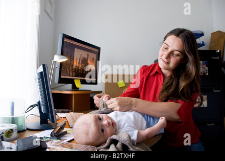 home office multitasking. modren office multitasking woman working mother juggles work in home office and  changing baby on her desk  inside t