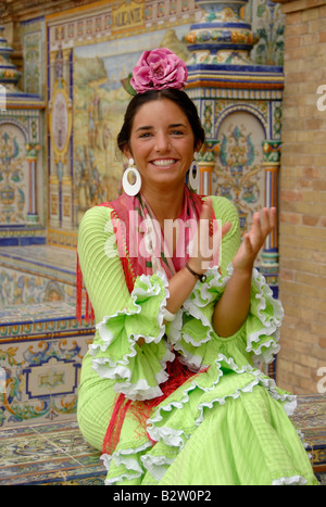 Seville fair Feria de Sevilla, young girl in traditional dress smiling and clapping - Stock Photo