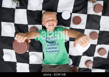 Boy on giant checkers board - Stock Photo
