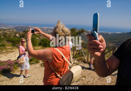 Tourists take photographs at mountain viewpoint near village of Kalamafka on the Greek Mediterranean island of Crete - Stock Photo