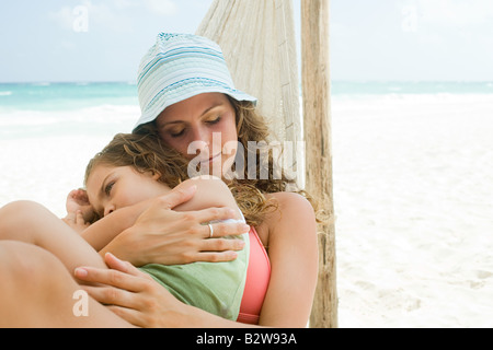 A mother and daughter sleeping on a hammock - Stock Photo