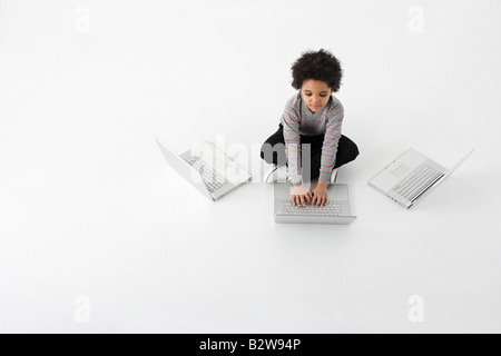 Boy with three laptops - Stock Photo