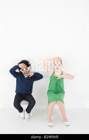 Boy and girl in 3D glasses - Stock Photo