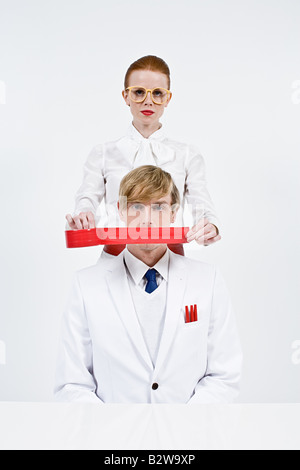 A woman covering a mans mouth with red tape - Stock Photo