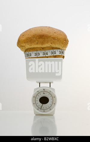 A loaf of bread on weight scales - Stock Photo
