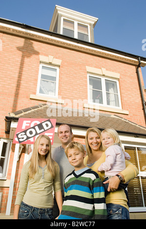 Family outside new house - Stock Photo