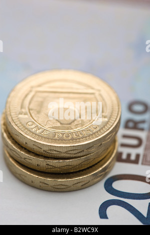 Pound coins on euro note - Stock Photo