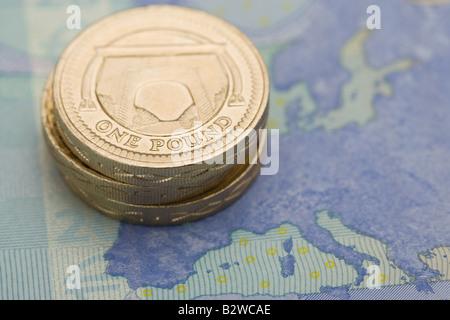 Pound coins on euro note - Stock Photo