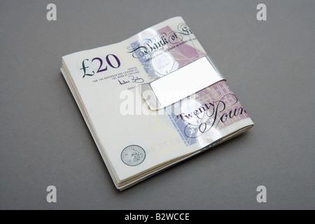 Twenty pound notes in money clip - Stock Photo