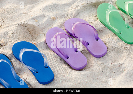 Flip flops in a row on a beach - Stock Photo