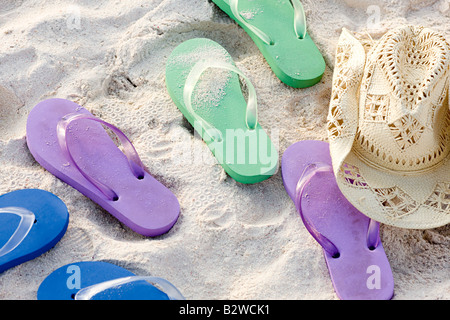 Flip flops and a sun hat on a beach - Stock Photo